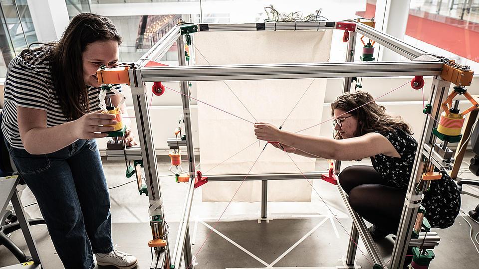 Zwei Studentinnen experimentieren mit einem quadratischen Gestell und Schnüren.