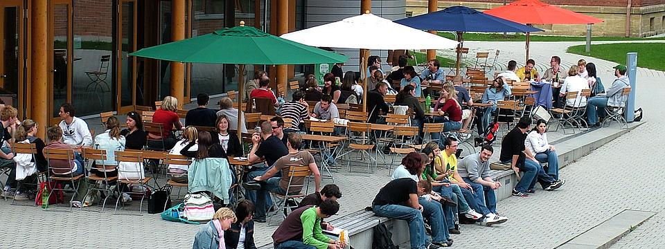 Außenbereich der Hochschule Ansbach mit Studenten unterm Sonnenschrim