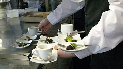 EIn Kellner nimmt mehrere Kaffeetassen.