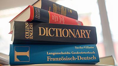 Verschiedene Wörterbücher die übereinander gestapelt sind.