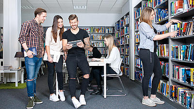 Studierende stehen in einer Bibliothek und tauschen sich über Inhalte auf einem Tablet aus.