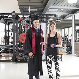 Zwei junge Menschen stehen in einem Fitnessstudio. Die junge Frau trägt Sportklamotten, der junge Mann einen Doktorhut und Robe.