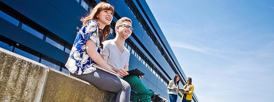 Zwei Studierende sitzen auf einer Mauer vor der Hochschule.