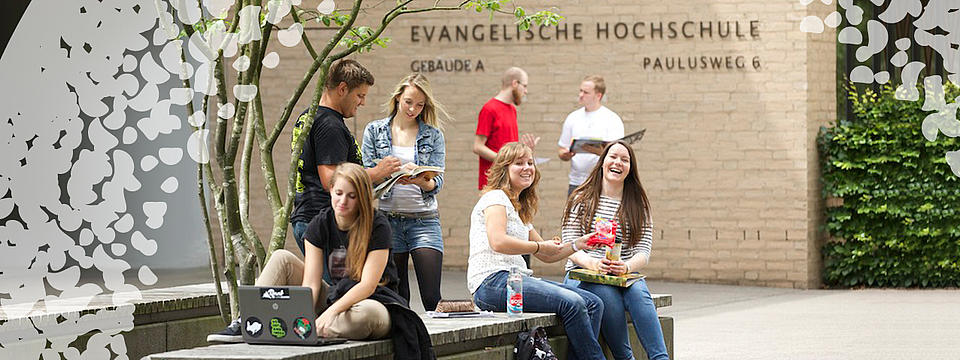 Studierende sitzend vor der Hochschule