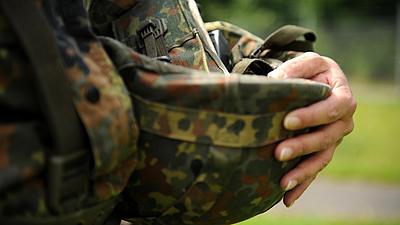Ein Soldat hält seinen Stahlhelm in der Hand.