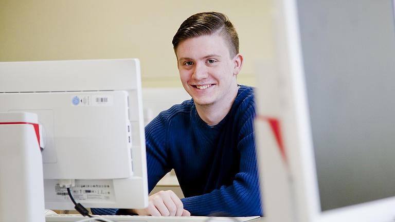 Ein Studierender sitzt an einem Bildschirm.