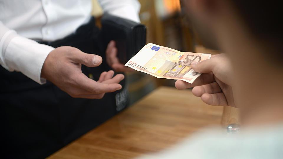 Restaurantgäste bezahlen beim Kellner.