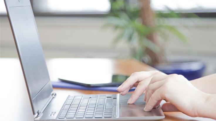Ein Laptop steht aufgeklappt auf einem Holztisch, die Hände einer Person arbeiten auf dem Touchpad