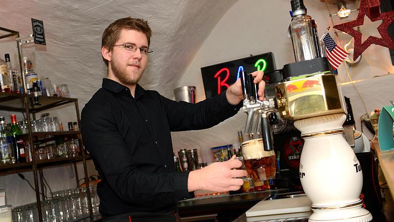 Ein Barkeeper zapft Bier in einer Kneipe.