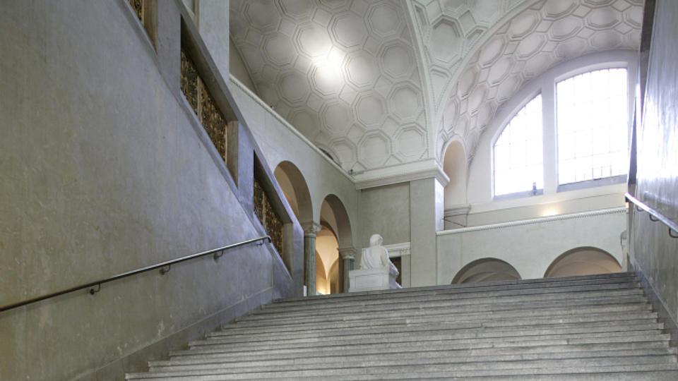 Zu sehen ist ein ehrwürdiges, marmornes Treppenhaus in einer Universität.