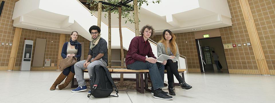 Vier Studierende sitzen auf einer Bank.