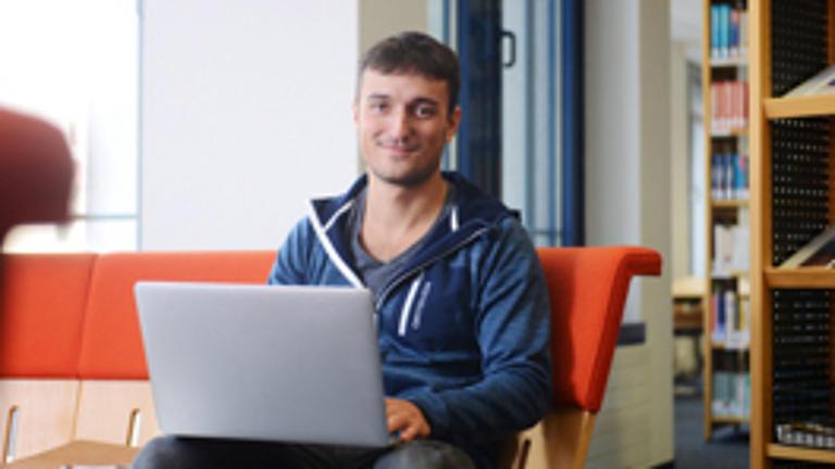Ein junger Mann sitzt mit Laptop auf einer Couch.