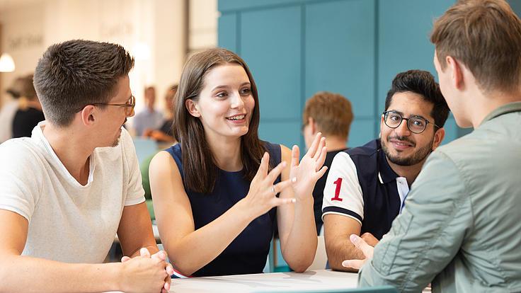 Studenten unterhalten sich am Tisch sitzend