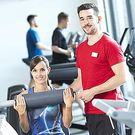 Zwei junge Menschen in einem Fitnessstudio.