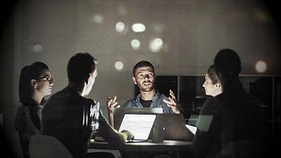 Eine Gruppe Studenten sitzend am Tisch. Einer erklärt etwas.