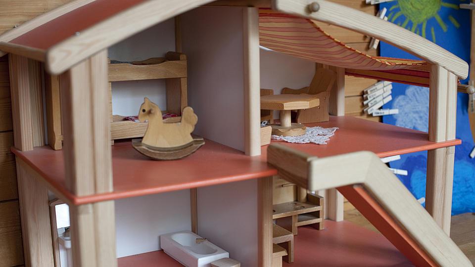 Aufnahme von einem Puppenhaus mit vier verschiedenen Zimmern, bestückt mit wenigen Puppenhausmöbeln.