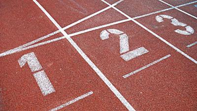 Detailaufnahme der Startplätze eins, zwei und drei auf einer roten Tartanbahn.