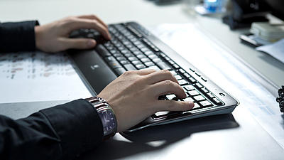 Zwei Hände tippen auf eine schwarze Tastatur.