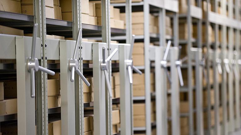 Seitlicher Blick in einen Gang eines Archivs, auf der linken Seite stehen mehrere verschiebbare Regale, die mit braunen Archivkartons bestückt sind.
