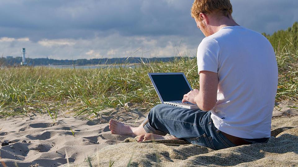 Student mit Laptop sitzend am Strand