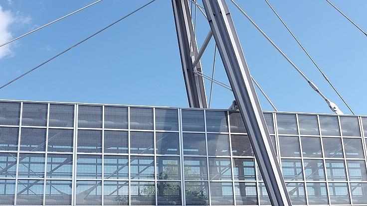 Zu sehen ist eine Stahlbrücke zwischen zwei Gebäuden.