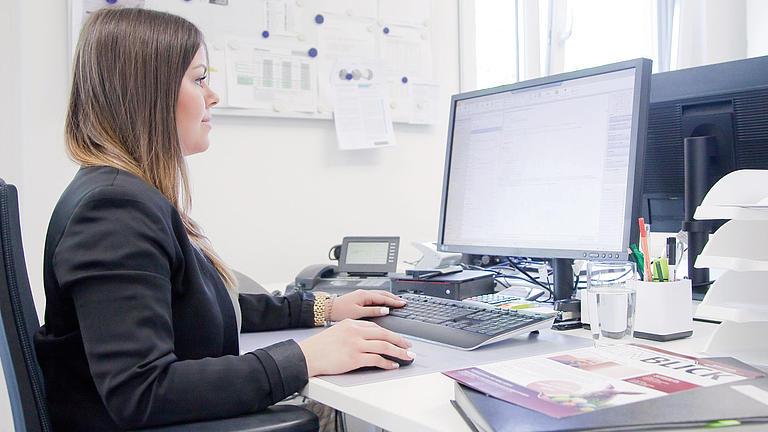 Eine junge Frau bearbeitet am Computer die Eingangspost