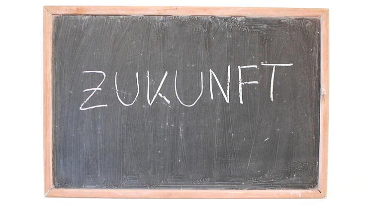 Auf einer Schreibtafel mit Holzrand steht in Großbuchstaben das Wort Zukunft.