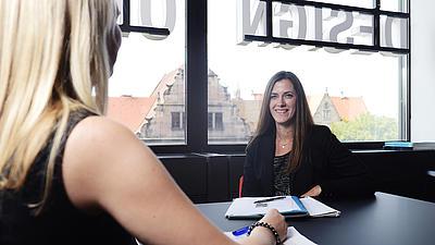 Vor einer großen Fensterfront sitzt eine junge Frau an einem schwarzen Besprechungstisch. Eine andere junge Frau sitzt ihr am Tisch gegenüber.