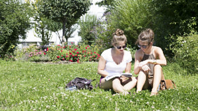 Zwei Studentinnen sitzen auf der Wiese und lernen.