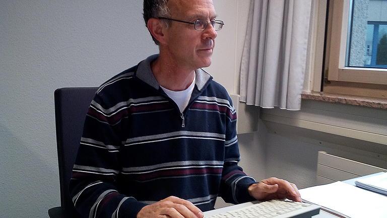 Foto von Reinhard Krämer am Schreibtisch.