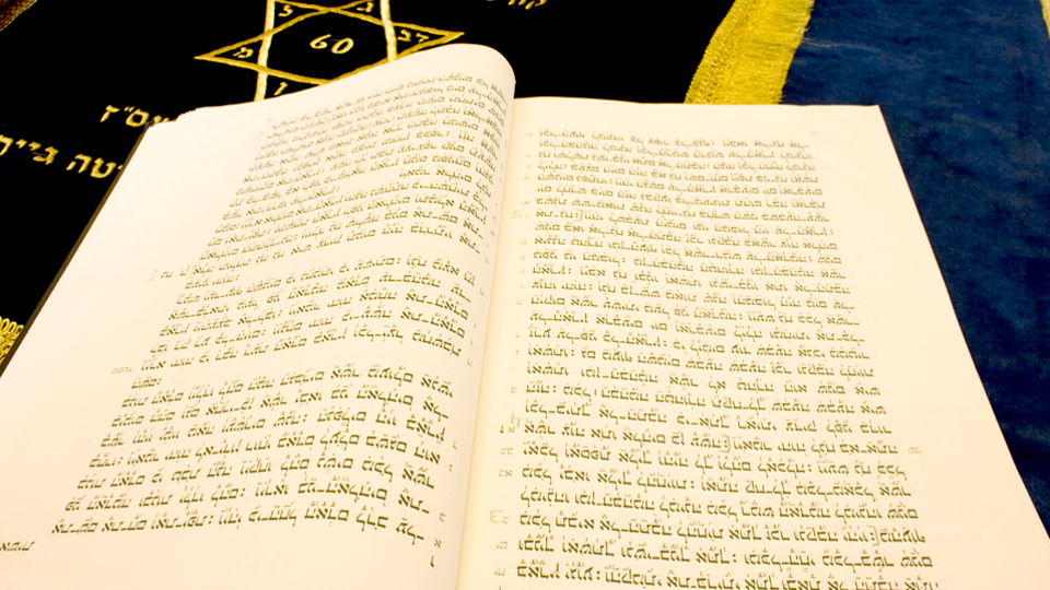 Zu-sehen-ist-ein-aufgeschlagenes-Buch-mit-Text-in-hebraeischer-Schrift