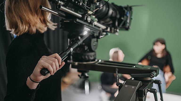 Zwei Studentinnen im Hintergrund werden von einer weiteren Studentin mit einer professionellen Kamera gefilmt