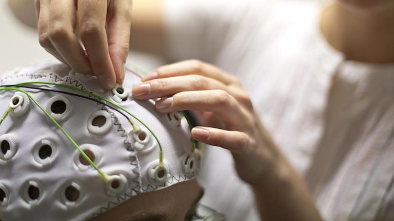 Nahaufnahme einer Frau die an einer Haube, die von einer Person getragen wird, Elektroden anschließt, um eine Hirnstrommessung durchzuführen.