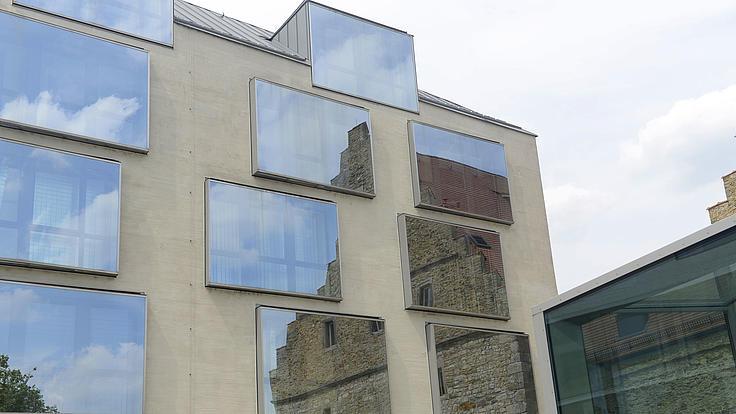 In den Fenstern eines modernen Gebäudes spiegelt sich ein altes Gebäude.