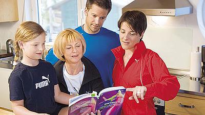 Zwei Studierende geben einer Mutter mit Kind Tipps für eine gesunde Ernährung.