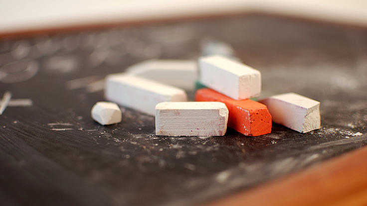 Auf einer holzumrahmten Tafel liegen mehrere weiße und ein rotes Kreidestück neben- und übereinander.