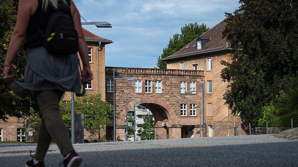 Universitätsgebäude mit einer laufenden Frau im Vordergrund