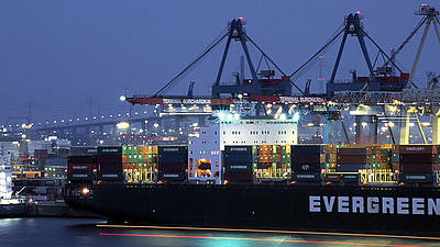 Ein im Hafen liegendes Frachtschiff wird in der Abenddämmerung beladen.