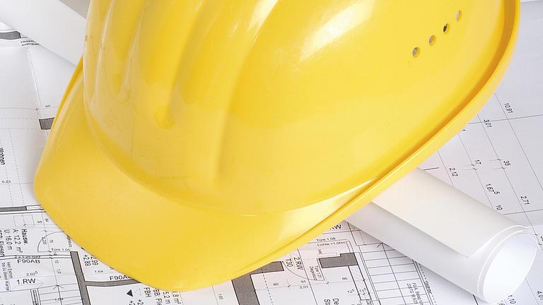 Auf einem aufgefalteten ausgebreiteten Bauplan liegt eine zusammengerollte Papierrolle, auf dieser liegt ein gelber Baustellenhelm.