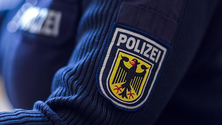 Nahaufnahme eines Polizeiwappens auf einem blauen Pullover am linken Oberarm einer Polizistin.