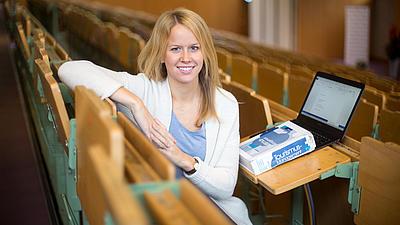 Studentin sitzt mit Laptop und Buch in einem Hörsaal.