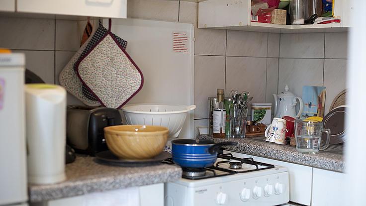 Blick in eine Miniküche mit verschiedenen weißen hängenden und stehenden Küchenschränken sowie einem Gasherd.