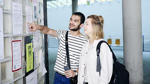 Eine junge Frau mit Rucksack und ein junger Mann stehen in einem Flur und schauen auf eine mit verschiedenen Dokumenten beklebte Wand.