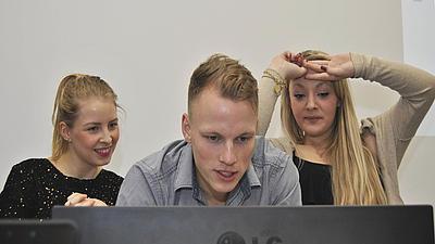 Drei Studierende sitzen gemeinsam vor einem PC-Bildschirm.