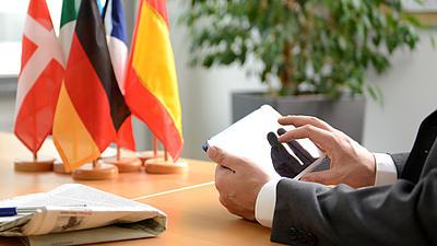 Jemand sitzt mit einem Tablet am Tisch auf dem verschiedene Flaggen stehen.