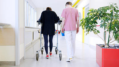 Junger Krankenpfleger hilft einer Patientin mit einer Gehhilfe bei Wiedererlernen des Gehens.