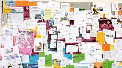 Nahaufnahme einer Pinnwand, die überladen voll ist mit verschiedensten bunten Zetteln, Flyern und Plakaten auf denen Sprachkurse, Vorträge, Partys und andere Aktivitäten angeboten werden.