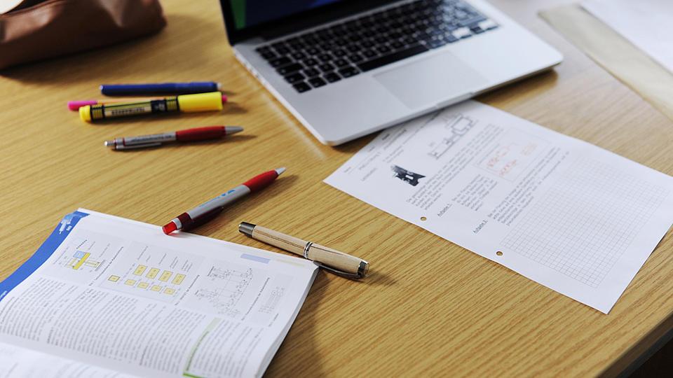 Auf einem Schreibtisch liegen verschiedene Schreibutensilien.