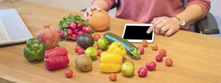 Verschiedene Gemüsesorten liegen auf einem Tisch, dahinter ein Man mit einem Tablet