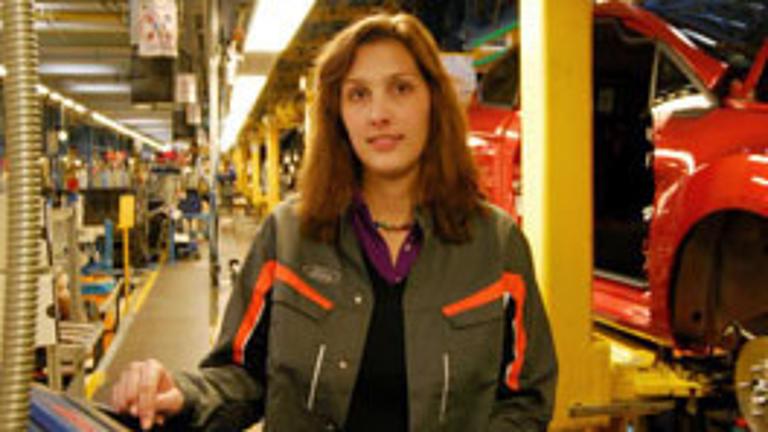 Eine Studierende steht in einer Autowerkstatt.